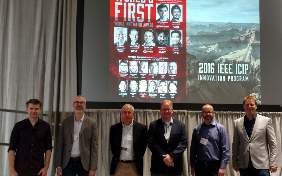 Six men designated as speakers for the 2016 IEEE Intl. Conference on Image processing are shown standing in front of a stage.