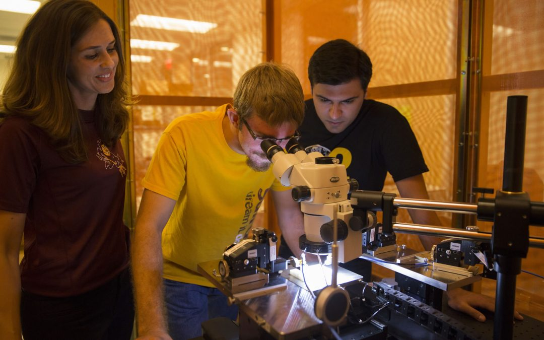 ASU Prof. Jennifer Kitchen with two young male students, one looking through microscope